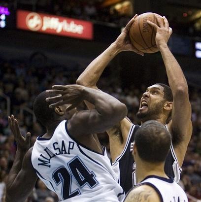 Tim Duncan avança sobre a marcação de Paul Millsap (AP Photo/Douglas C. Pizac)