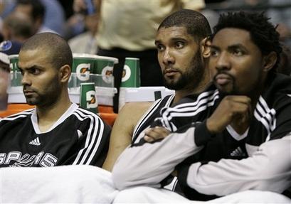 Com cara de poucos amigos, Parker, Duncan e Mason assistem ao último quarto do banco de reservas. (AP Photo/Tony Gutierrez)